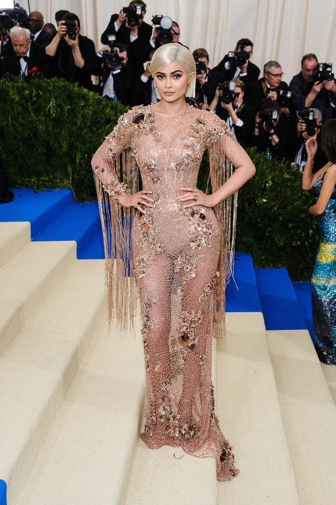 Kylie Jenner on the red carpet stairs the 2017 Metropolitan Museum of Art Costume Institute Gala in New York City sporting a platinum blonde wig.