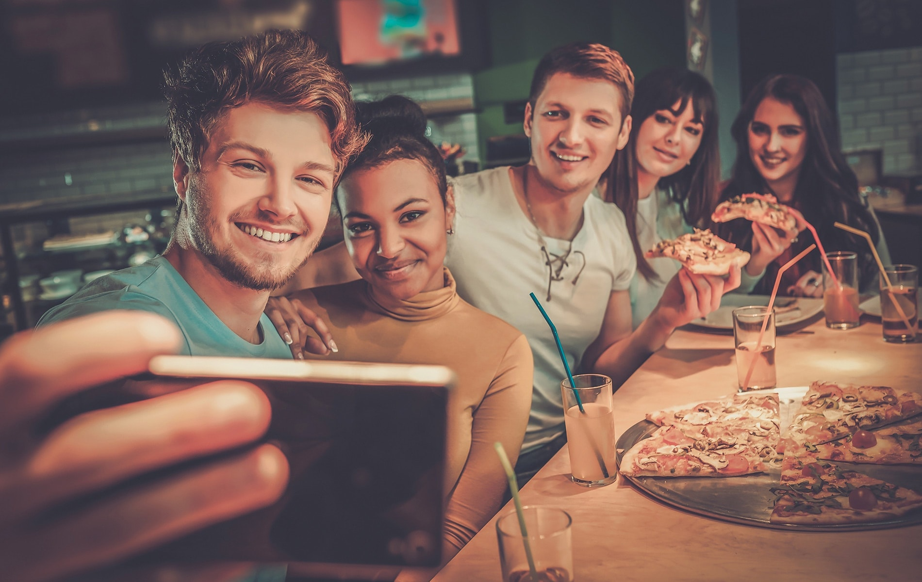 Cheerful group of five friends having fun eating pizza and taking a selfie.