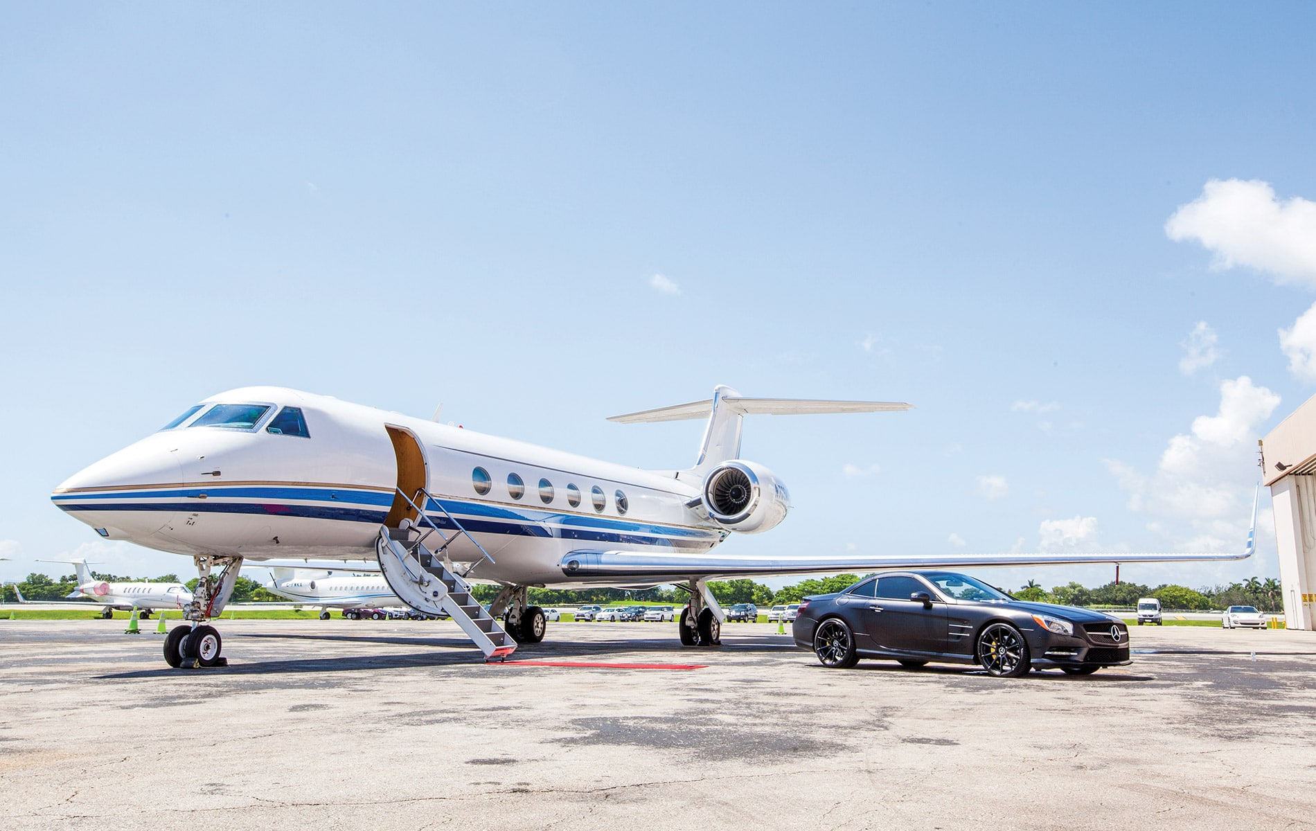 JetSmarter jet with a red carpet and a black car waiting at airport
