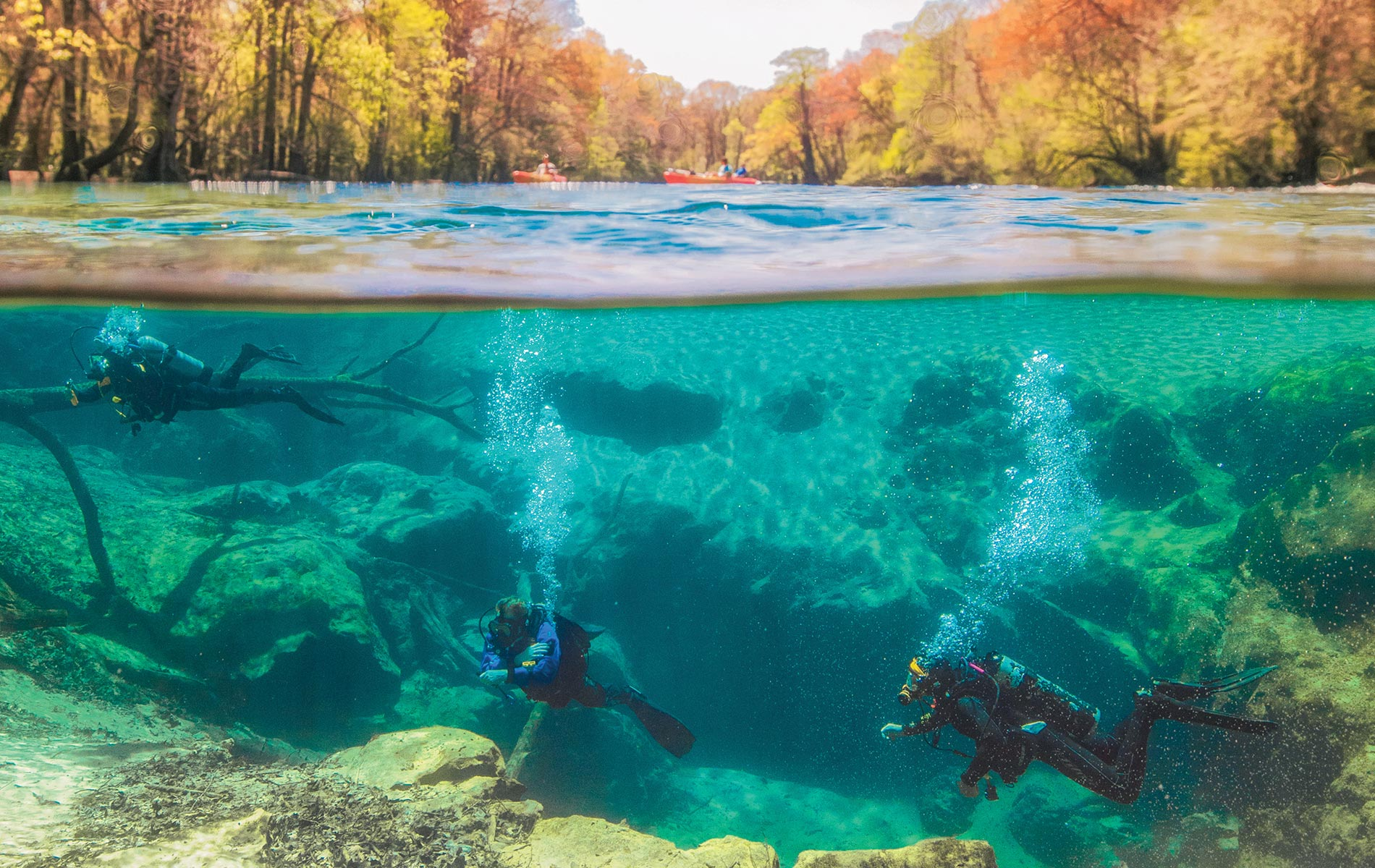 John Hott, Torrey Blackmon, and Laython Blackmon dive Cypress Springs while kayakers explore the surface.