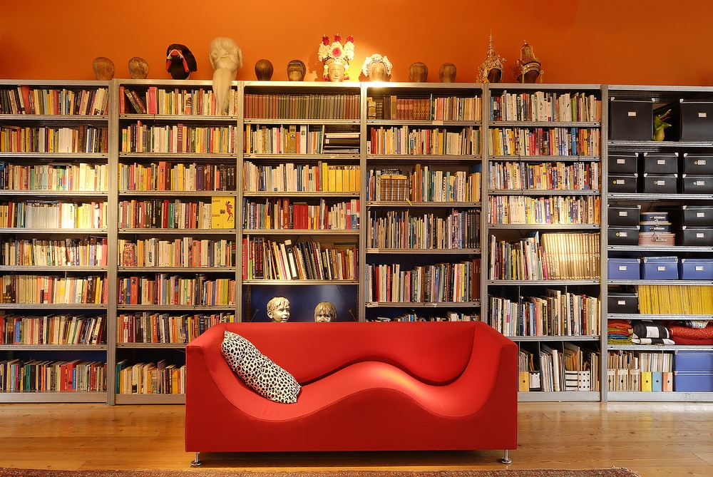 Large, orange library wall and a cozy, red couch make up a big portion of the family's living room in The Blue House.