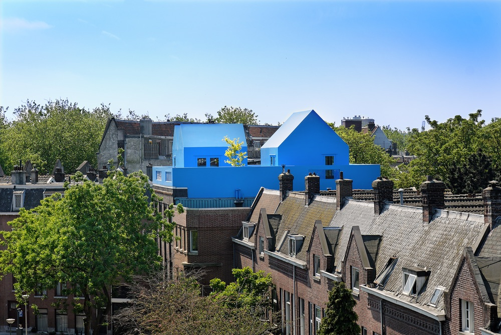 A rooftop view of The Blue House and its neighboring houses shows just how bright the blue stands out among the neutral shades of other houses on the street.