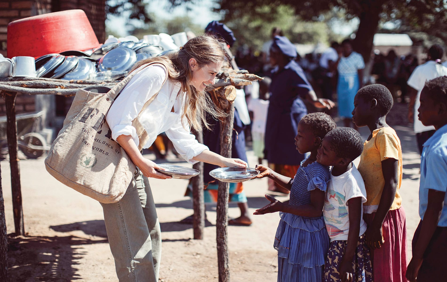Lauren Bush Lauren handing out plates to a line of small children with a FEED bag on her shoulder