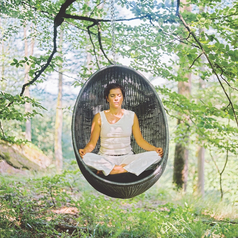 A woman meditating in a hanging seat in the forest at La Clairière in Alsace, France