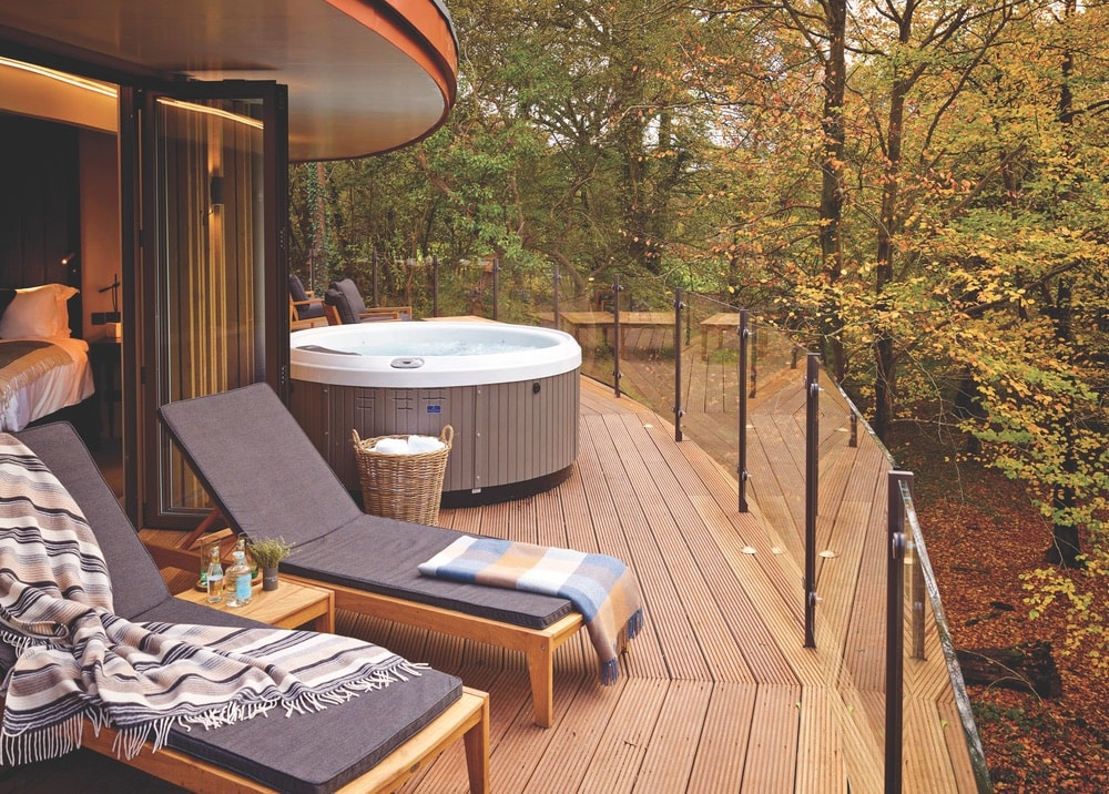A treehouse deck containing a hot tub and 2 lounge chairs right off of the bedroom at Chewton Glen Hotel & Spa in New Forest, England surrounded by trees