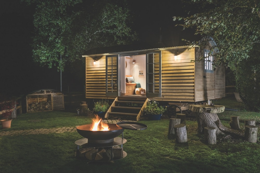 Quaint, hideaway cabin at the Fish Hotel in the Cotswolds, England with a campfire and fresh wood at night