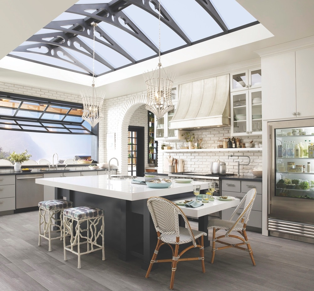This open-concept greenhouse kitchen created by Cheryl Kees Clendenon in collaboration with Kohler, Silestone, and Benjamin Moore embodies utilitarian design with sink and faucet pairings that create a sense of flow and stability.
