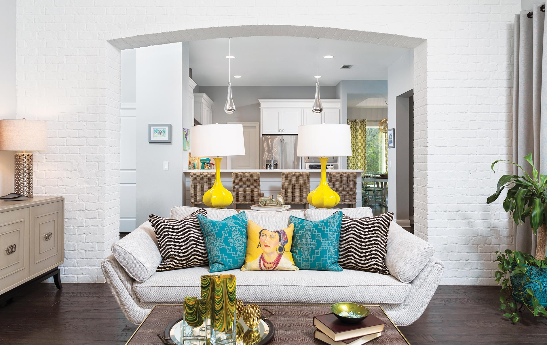 White painted brick is the perfect complement to colorful accents in this new construction home. Gorgeous lighting and proper placement of recessed can lights help create a bright and cheerful space with family in mind.