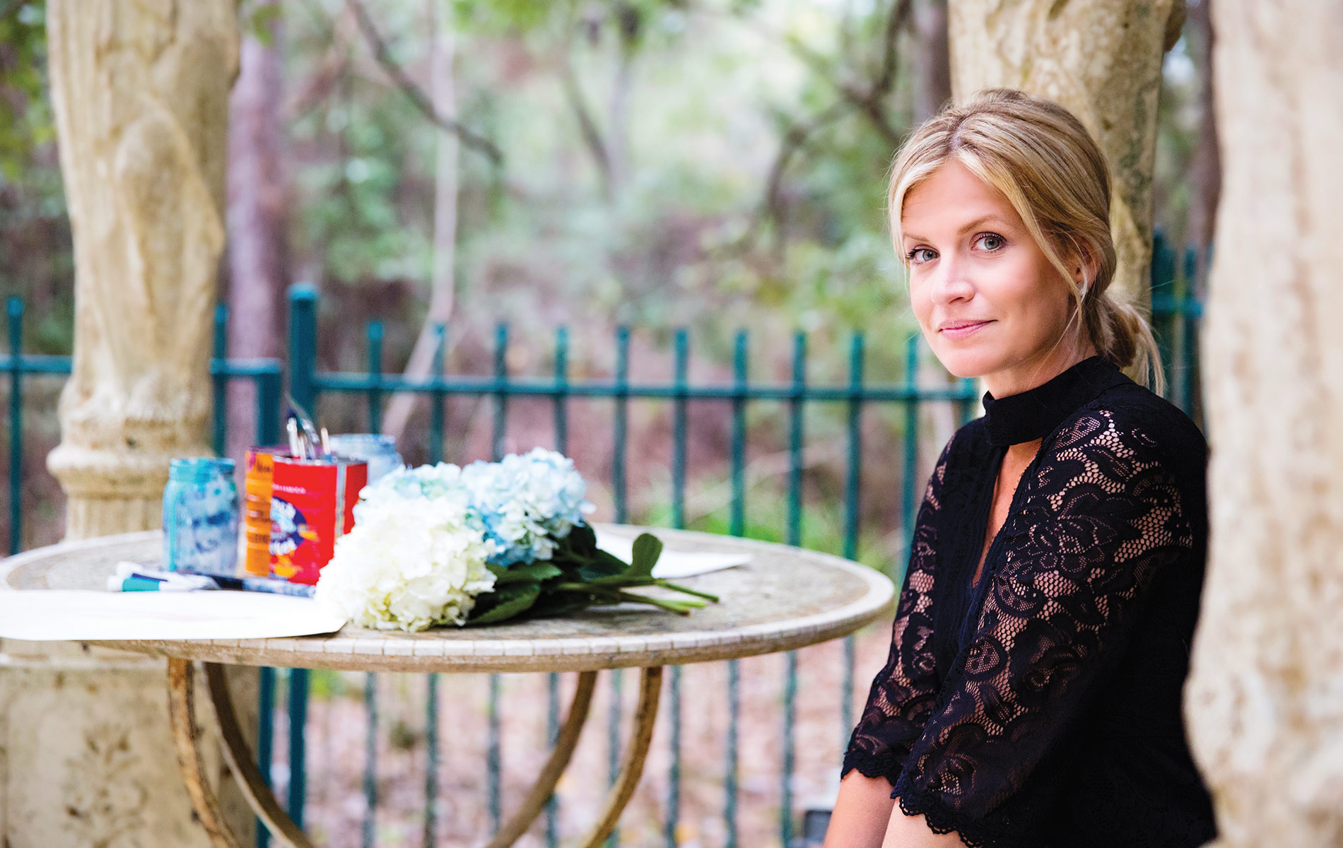 Artist Jessica Hathorn sitting in nature by a table that's topped with flowers and paint