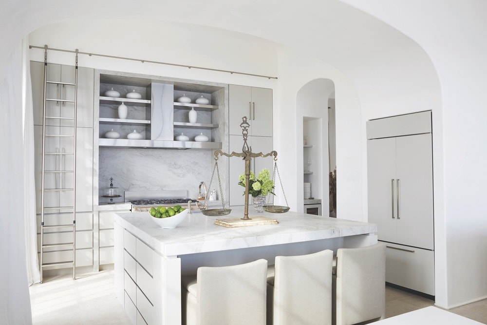 The sleek white of its facade is carried through in the Crockett Residence's kitchen, with an oversized island perfect for cooking and entertaining.