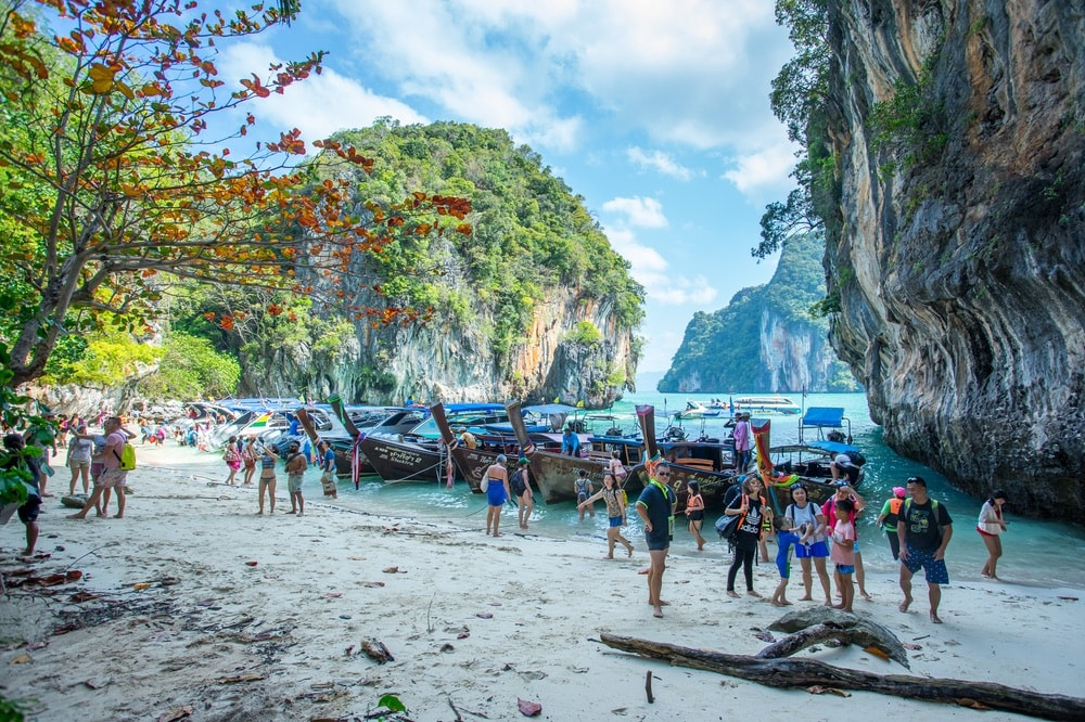 People arriving on an island by long tail boat and speed boat in Krabi Province Thailand.