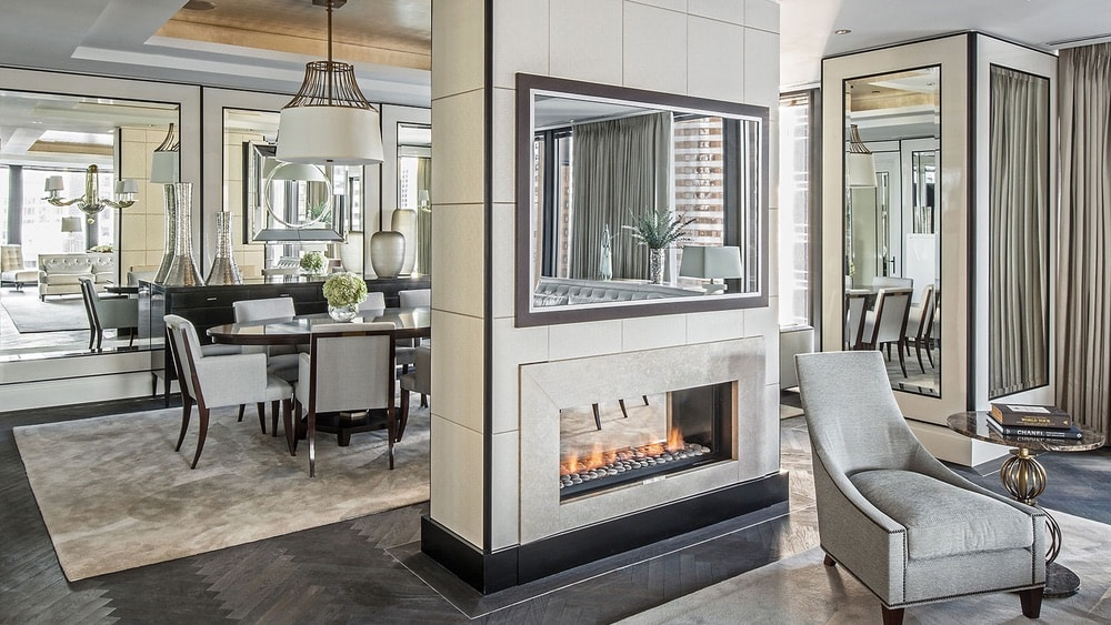 Regent Suite Dining Room at the Langham Hotel with a fire place and dinning table and mirrored covered walls