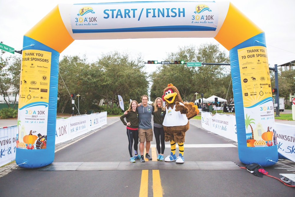 Co-race director Craig Baranowski (center) of Scenic Sotheby's International Realty stands in the Rosemary Beach intersection of Highway 30-A with 30A 10K Thanksgiving Day founders, Karen Meadows (right) and Amy Stoyles (left), at the 2017 race.