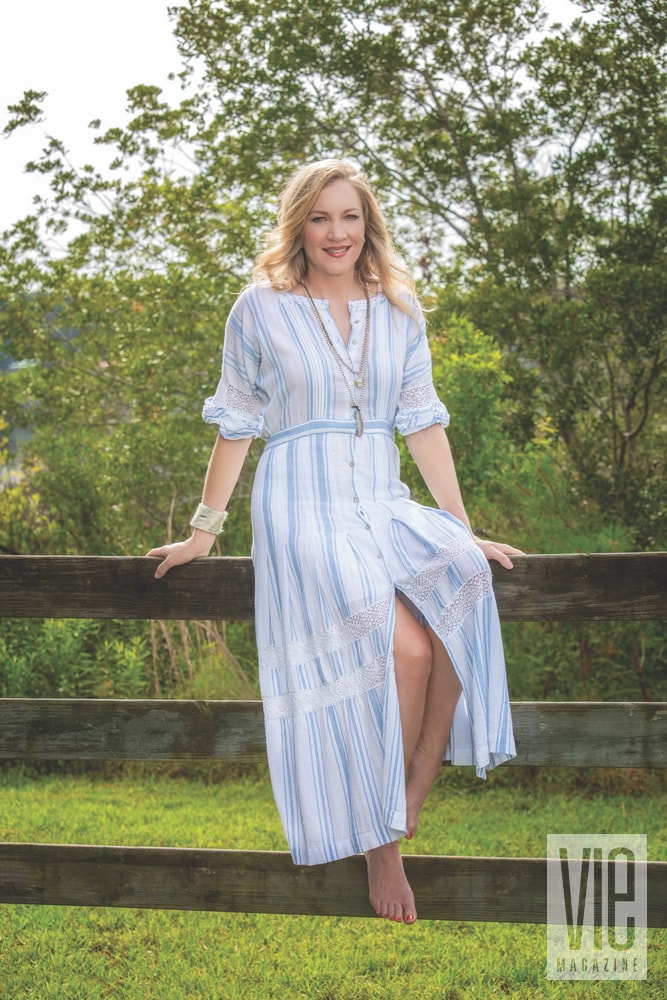 Hood sitting on a wood fence dress in a maxi dress from Kiki Risa