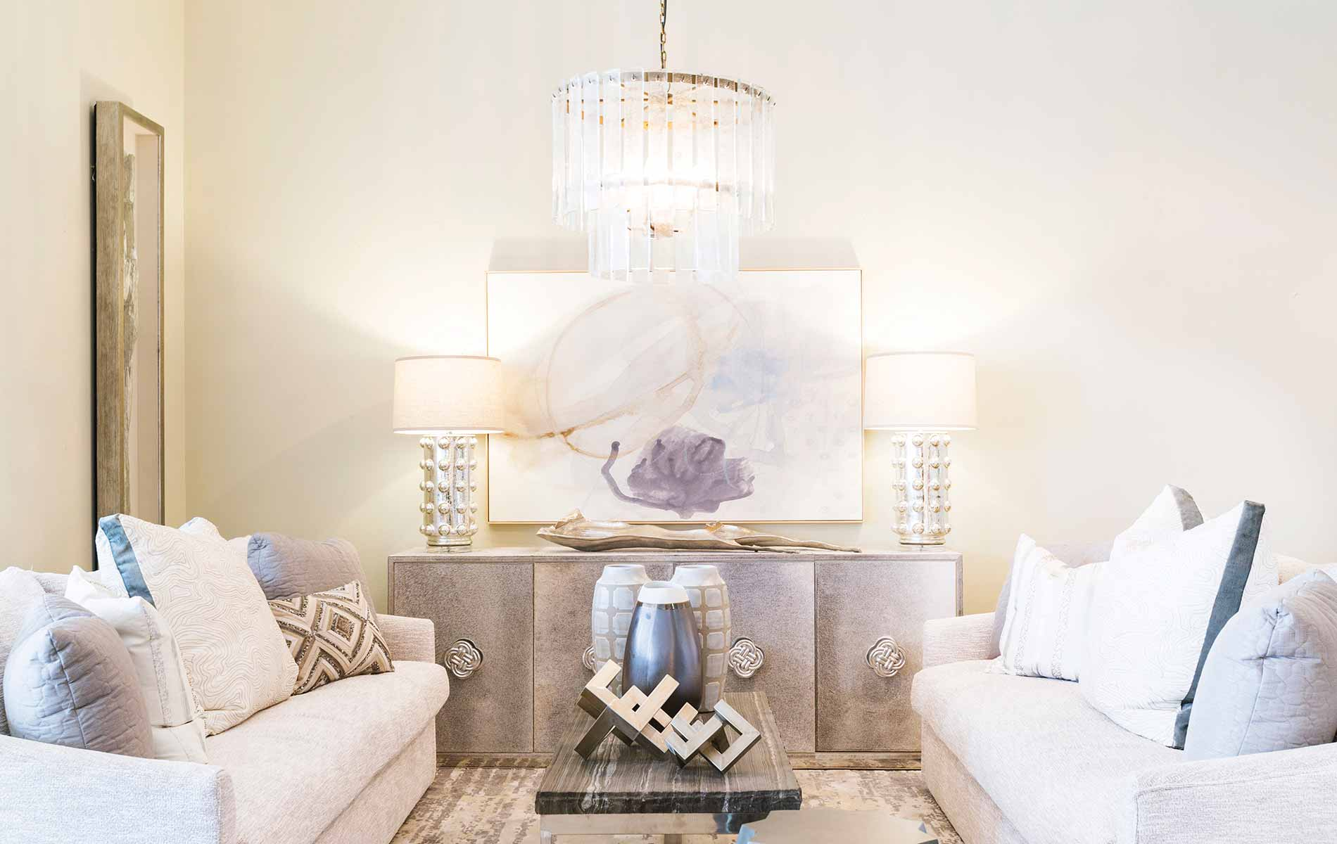 Glamorous elements are toned down with more casual textures and stone materials to create an earthy style in this living room designed by Lovelace Interiors. Heavy chenille fabrics warm up the cooler metals.