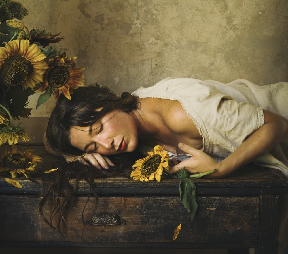 Photograph by Jamie Beck showing a female leaned over a table holding a sunflower