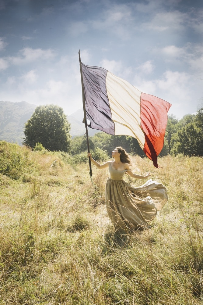 Photograph by Jamie Beck showing a female in a field holding a large French flag