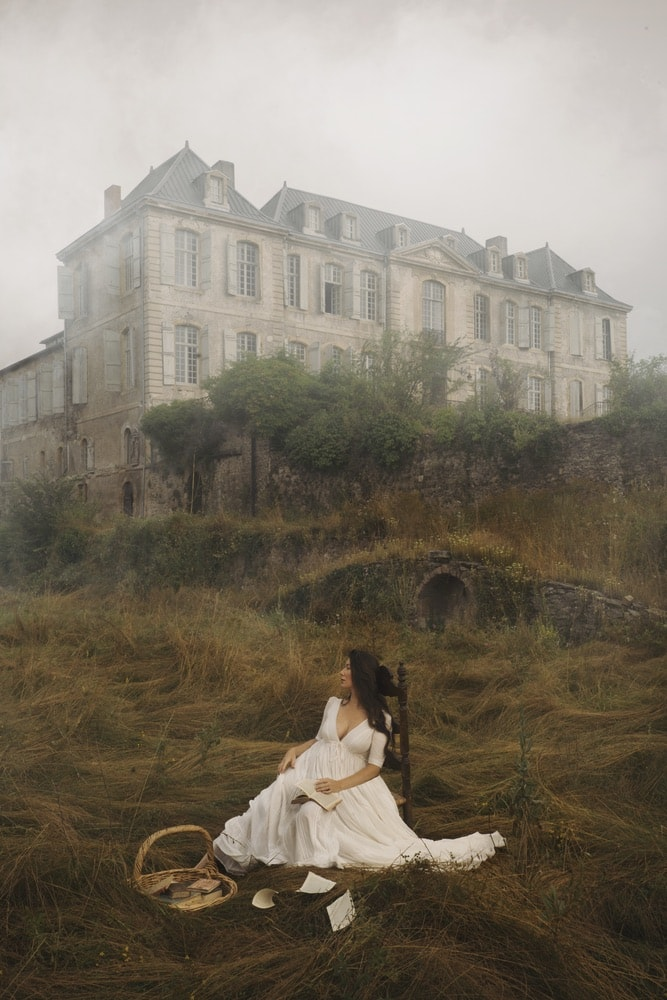 Photograph by Jamie Beck showing a female sitting in a chair in front of a large French house