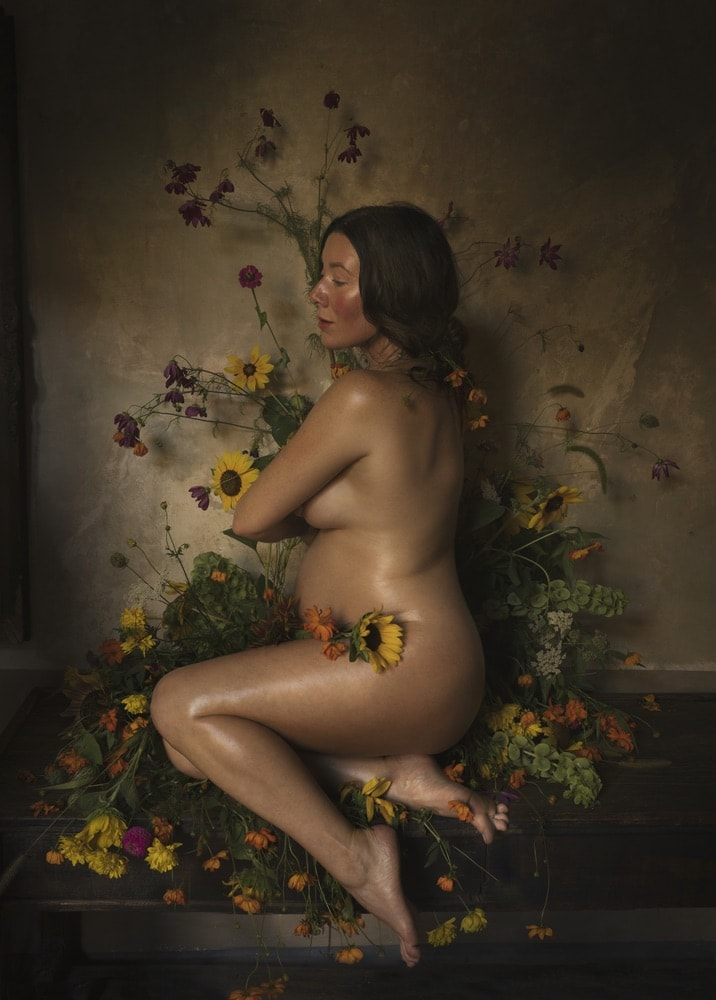 Photograph by Jamie Beck showing a pregnant female covering her body with her arms and flowers