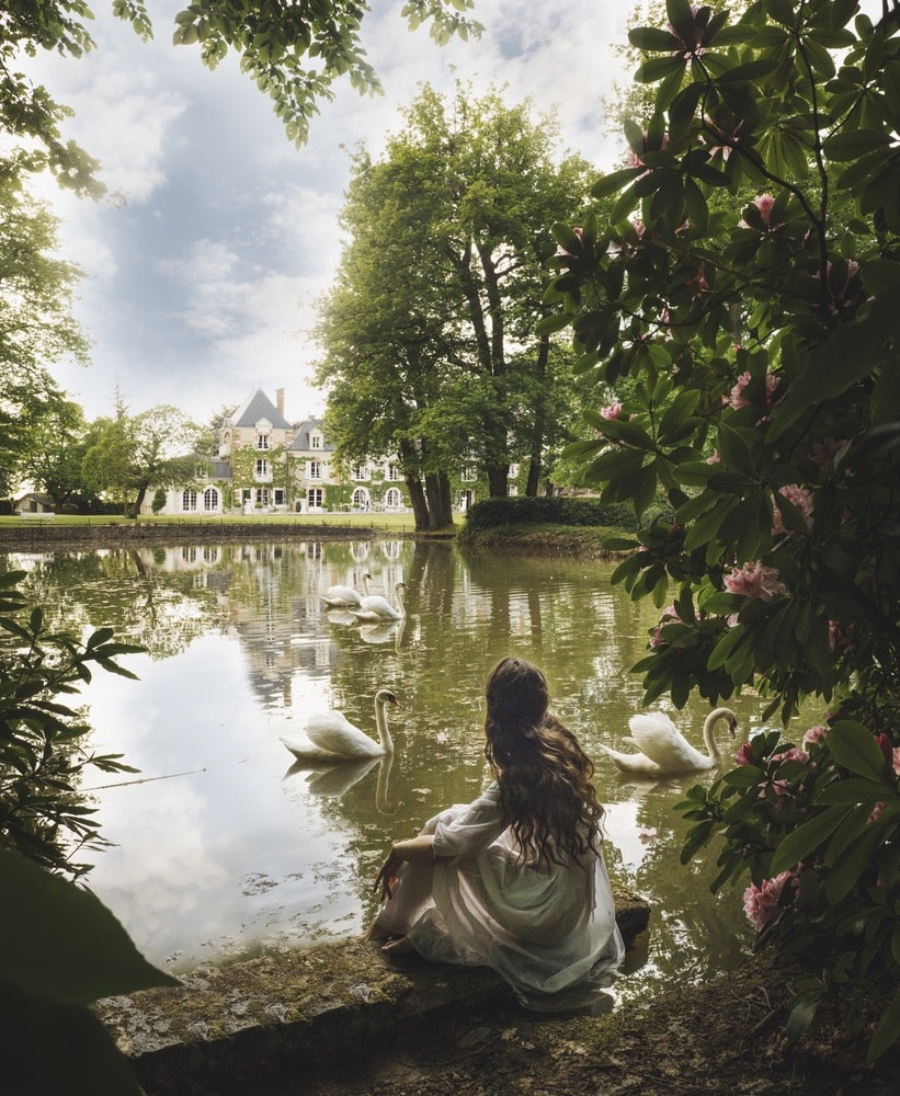 Photograph by Jamie Beck showing a female sitting on the edge of a pond surrounded by plants overlooking a large French estate and swans