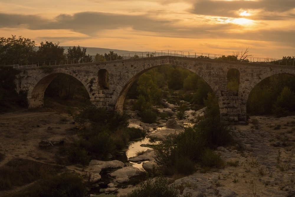 Photograph by Jamie Beck showing an older, brick bridge in Provence France at dusk