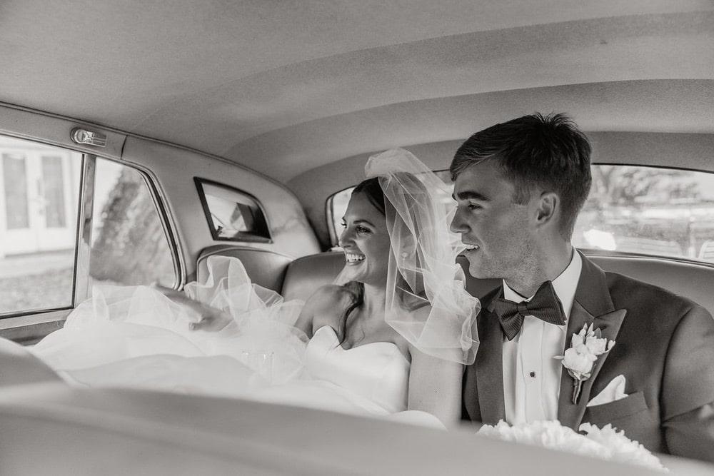 Ellie Romair and Alex Alford sitting in a vintage car