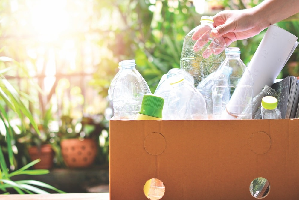 Plastic bottle garbage being put in recycling for reuse