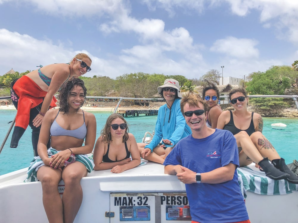 Divemaster Loys, Michelle, Stephanie, Romona, Divemaster Floris, Rana, and Breanna take a break after exploring the western side of the island with Go West Diving
