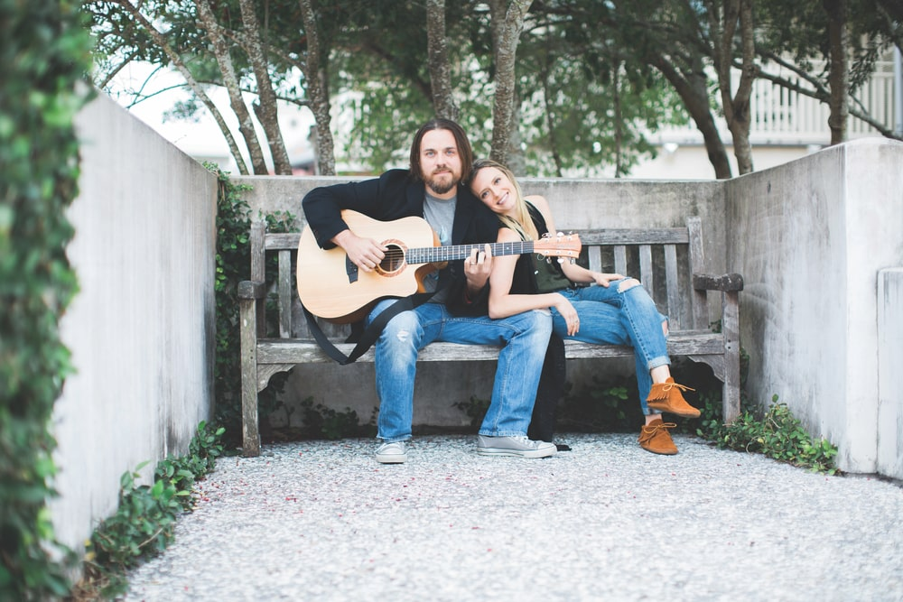 Will and Lindsey Thompson sitting outside on a bench playing guitar