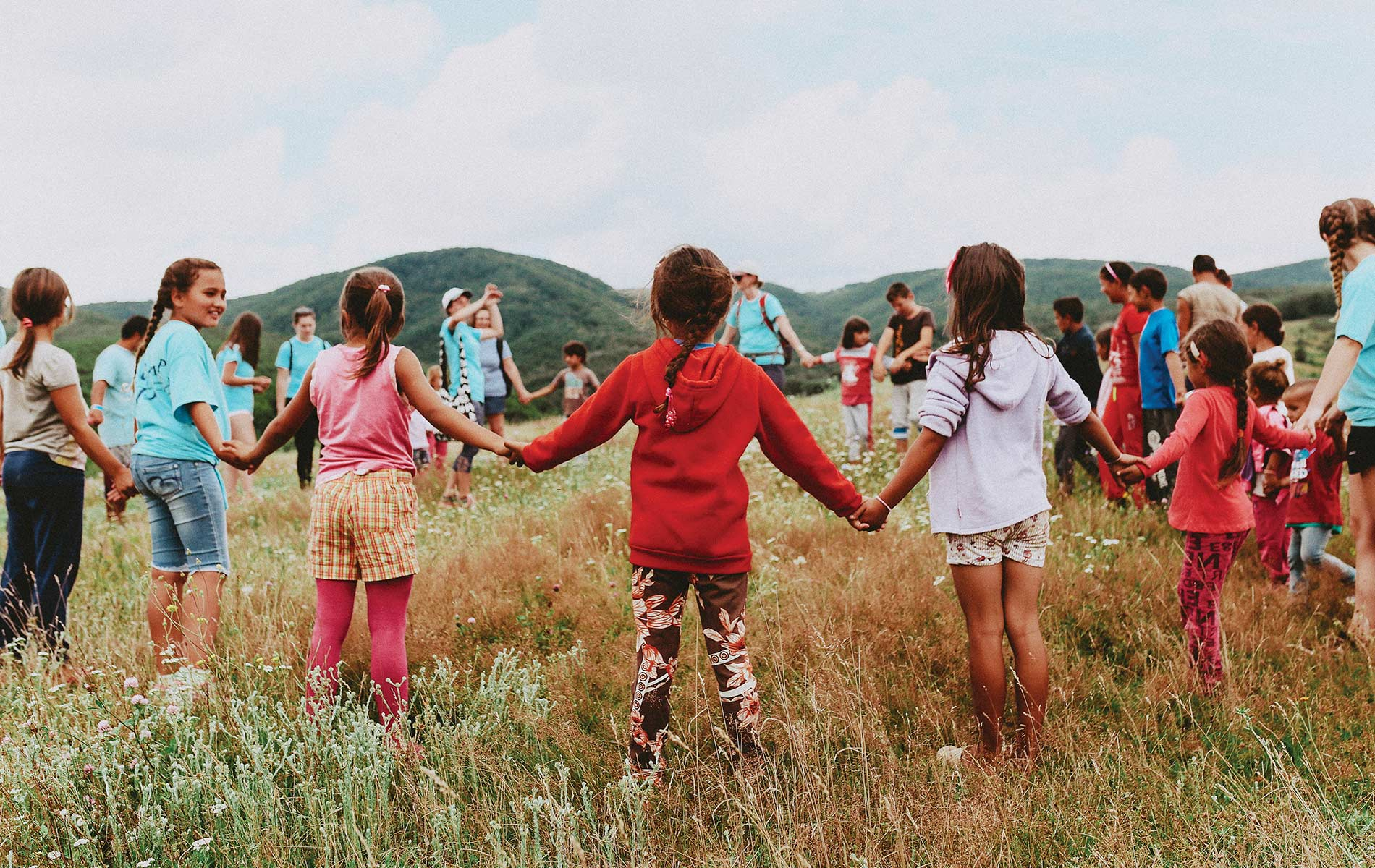 Children in a field holding hands