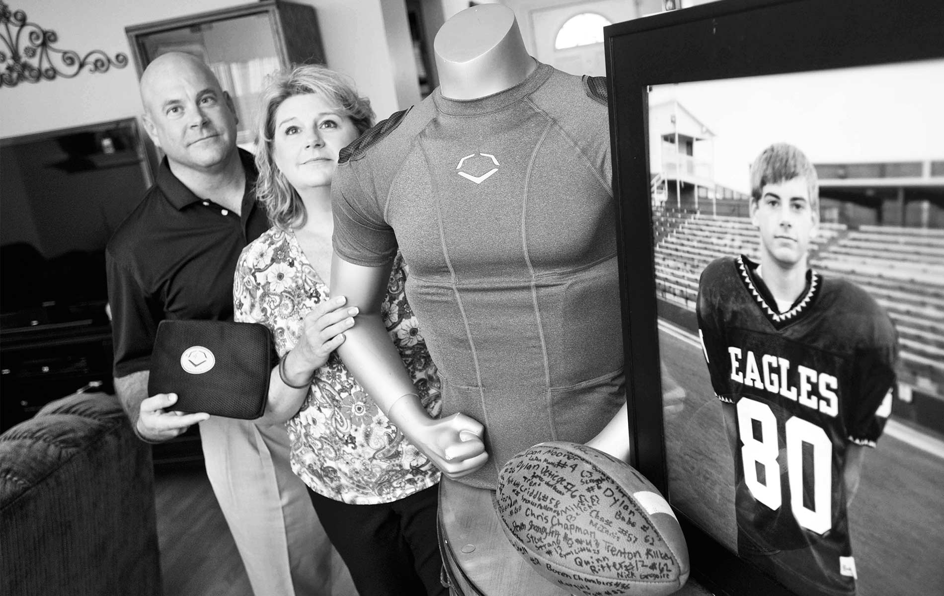 Brian and Kathy Haugen display the rib-protecting shirt that could have saved their son's life. Now they dedicate funds from the Taylor Haugen Foundation to equipping young athletes with this and other protective gear. | Photo courtesy of Taylor Haugen Foundation
