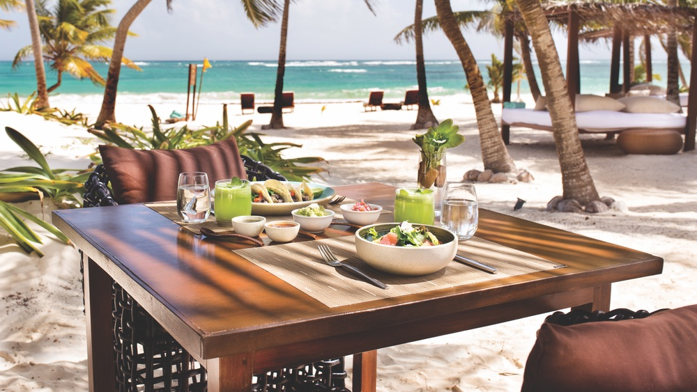 Table full of foods like green juices and salads to authentic tacos and more on the beach at Mukan Resort