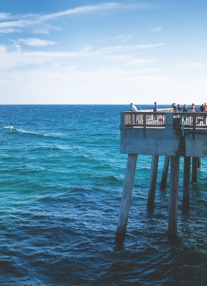 View of the gorgeous blue, Gulf of Mexico waters and fisherman fishing off of a large pier in Panama City Beach, Florida.