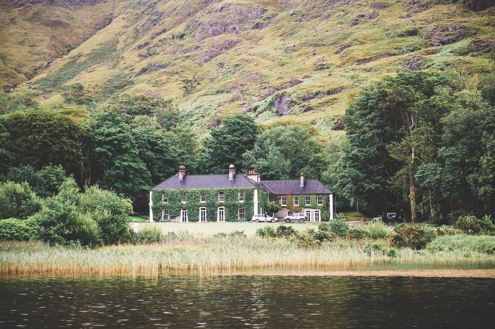 Beautiful ivy two-story home sitting on the edge of the water at the foothills of a mountain in Ireland