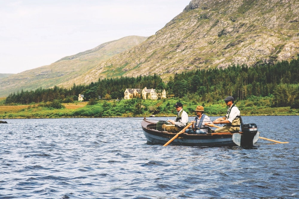 Three men fishing in one boat with a large house on the shoreline and mountains in the distance