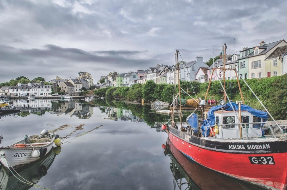 View of a few boats and many pastel colored homes in Roundstone Harbour, Ireland