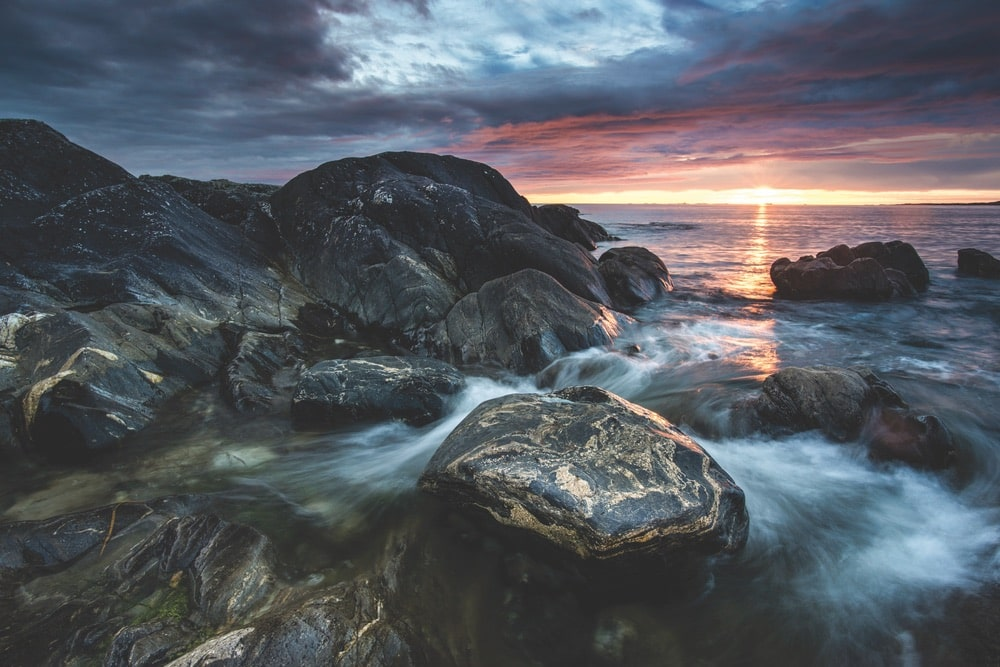 View of the Errislannan shoreline, dark rocks, and stormy clouds at sunset in Ireland