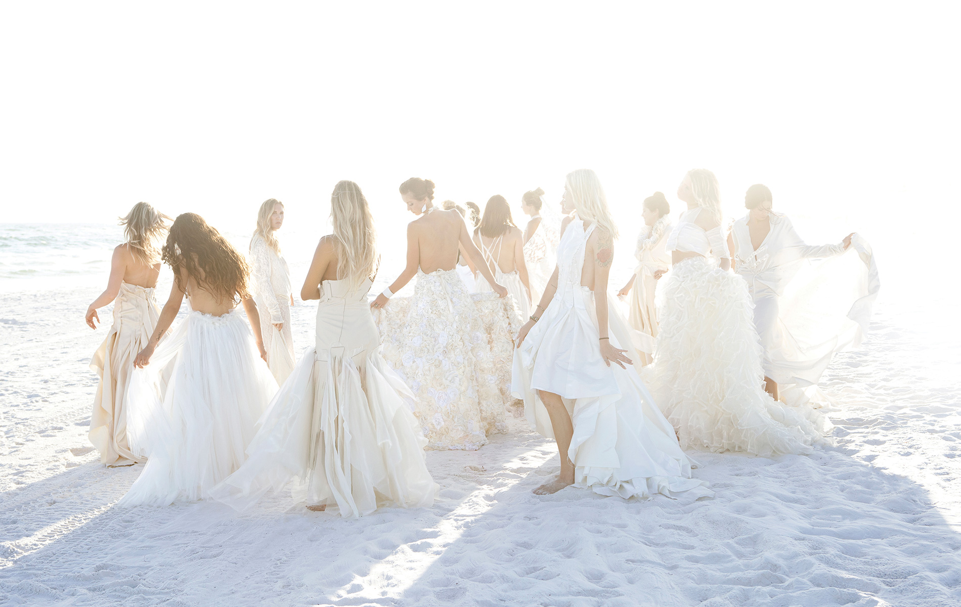 Nicole Paloma Bridal, group shot of models in wedding gowns on the beach