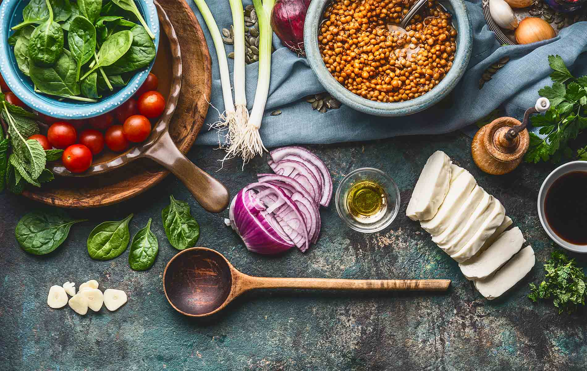Vegetarian ingredients for tasty lentil dishes on rustic kitchen table background with cooking spoon and utensils, top view, border. Healthy eating and cooking, clean or diet food concept