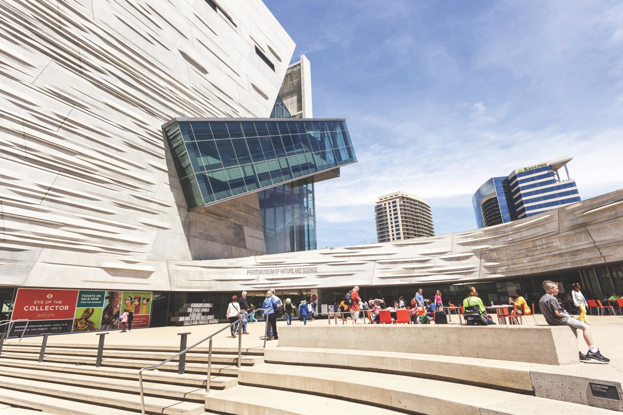The Perot Museum of Nature and Science in Dallas has a modern exterior with people enjoying a beautiful sunny day.