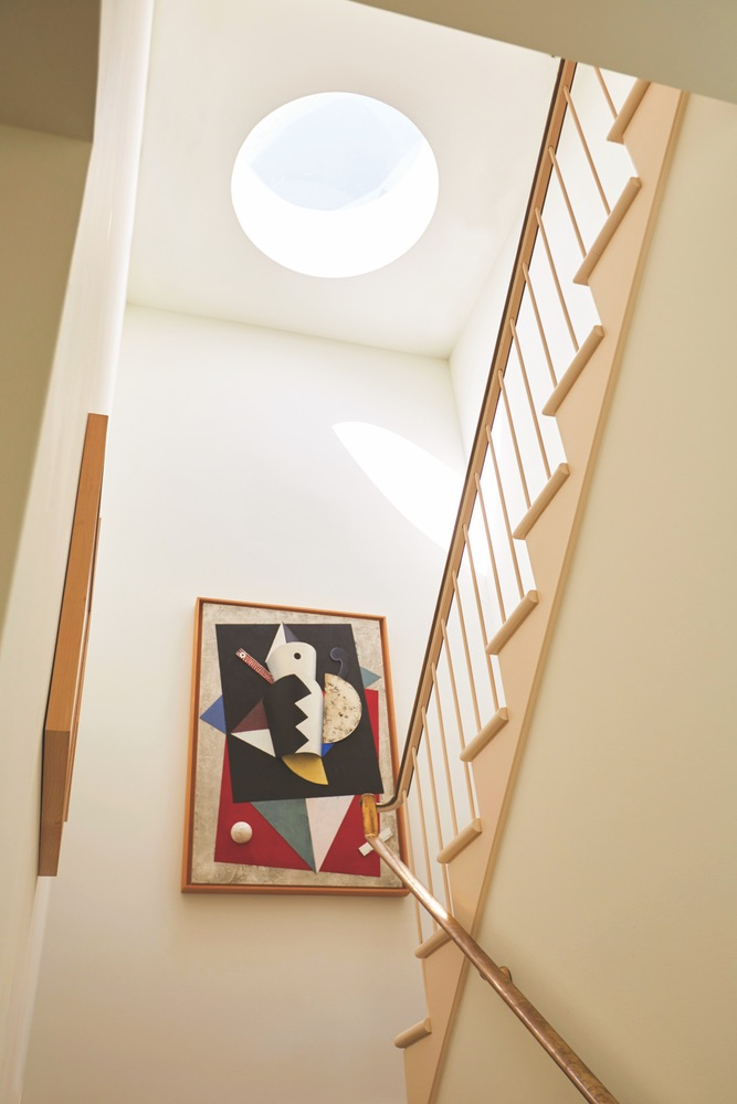 Art on the wall in the stairwell with a natural light pouring through the skylight at Paula Lambert's Turtle Creek home in Dallas, Texas