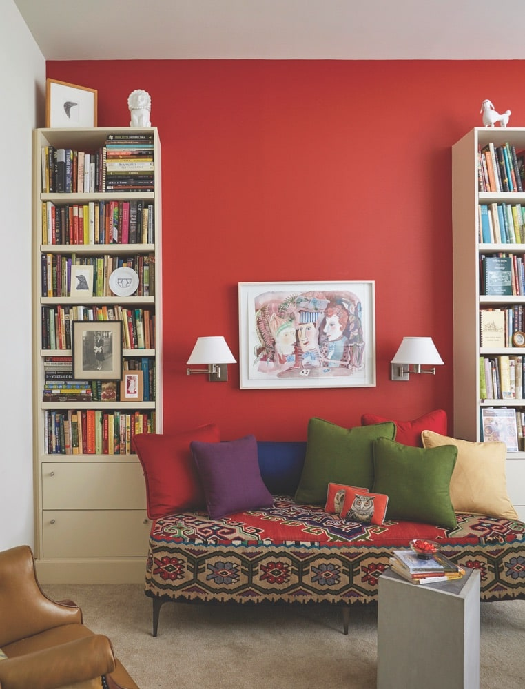 A sitting area in Paula Lambert's home office with red walls, bookshelves full of books, and a fun-patterned lounge couch at her Turtle Creek home in Dallas, Texas