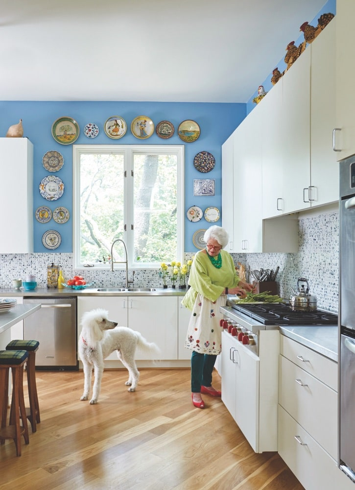 Paula Lambert in her blue and white kitchen prepping food with her white dog at her Turtle Creek home in Dallas, Texas