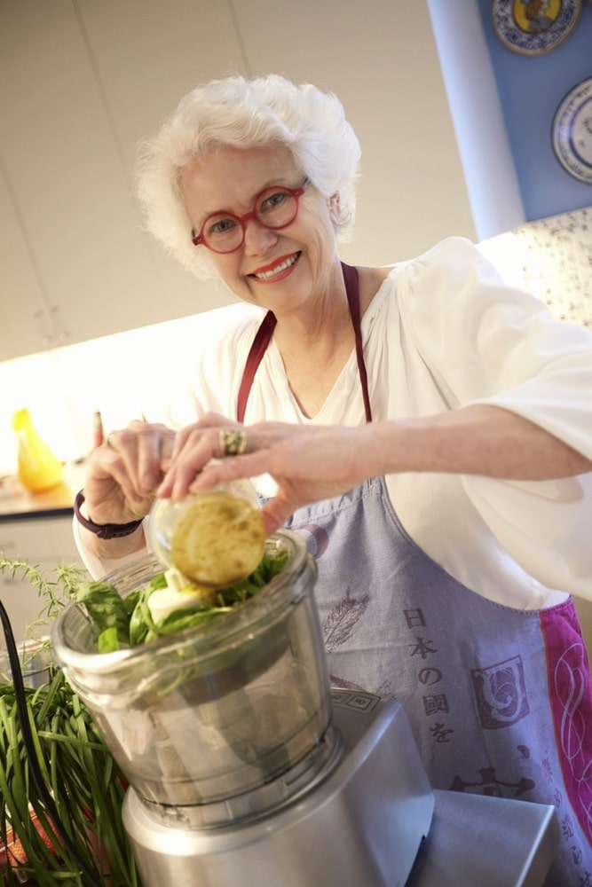 Paula Lambert prepping some pesto to serve at her dinner party at her Turtle Creek home in Dallas, Texas