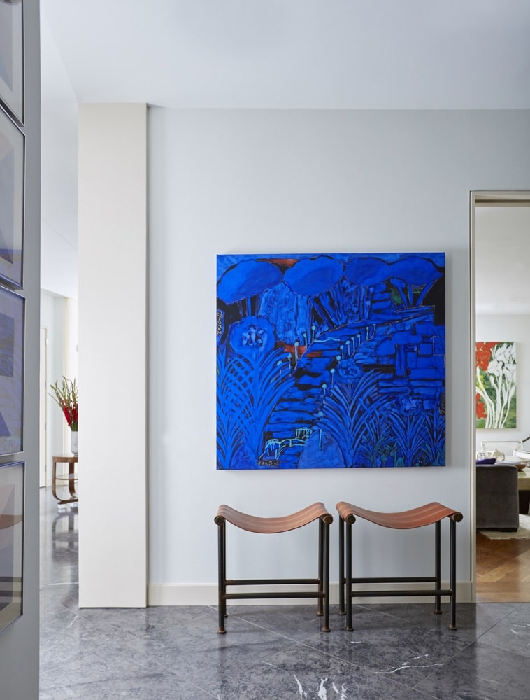 Beautiful, blue painting sitting above 2 chairs in the hallway at Paula Lambert's Turtle Creek home in Dallas, Texas