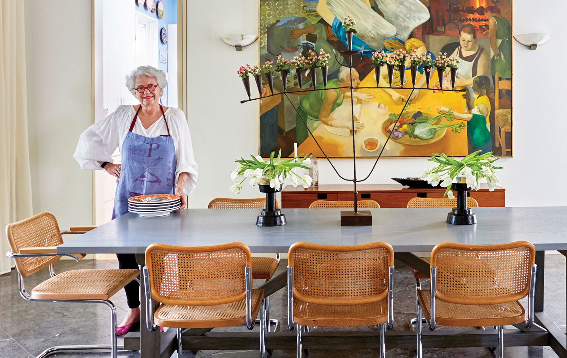 Paula Lambert standing in her dining room with flatware to arrange on her table at her Turtle Creek home in Dallas, Texas