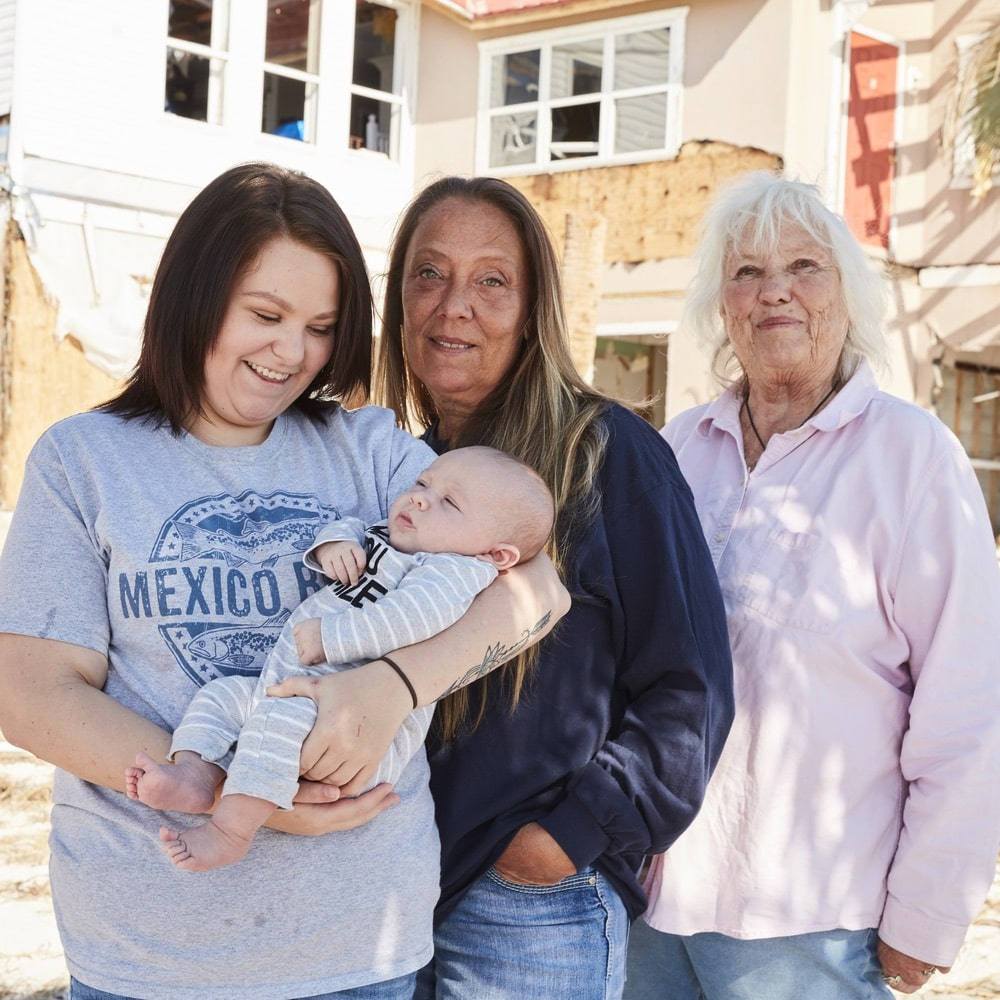 Kenzie (with baby Maverick), Shawna, and Peggy Wood stand outside the remains of the Driftwood Inn in Mexico Beach Florida from Hurricane Michael