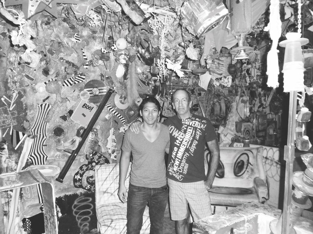 Black and white image of Robbie Antonio with L.A.–based artist Kenny Scharf standing in front of Kenny's artwork
