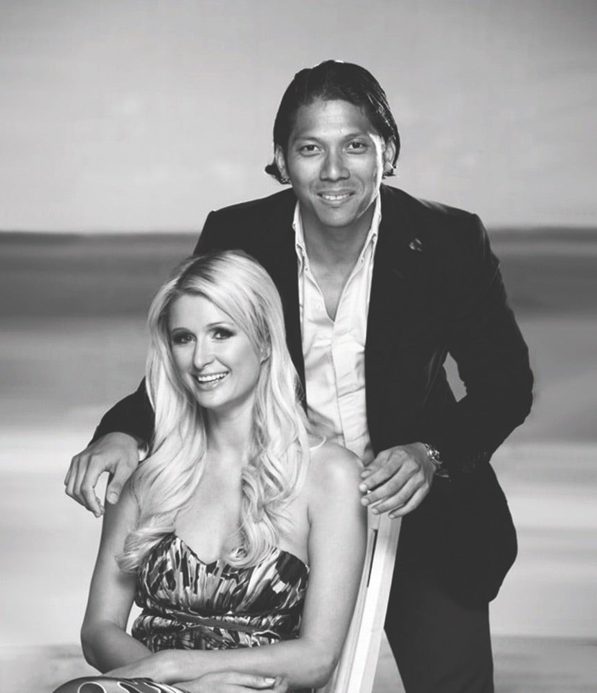 Black and white image of Robbie Antonio posing behind Paris Hilton, who is sitting down