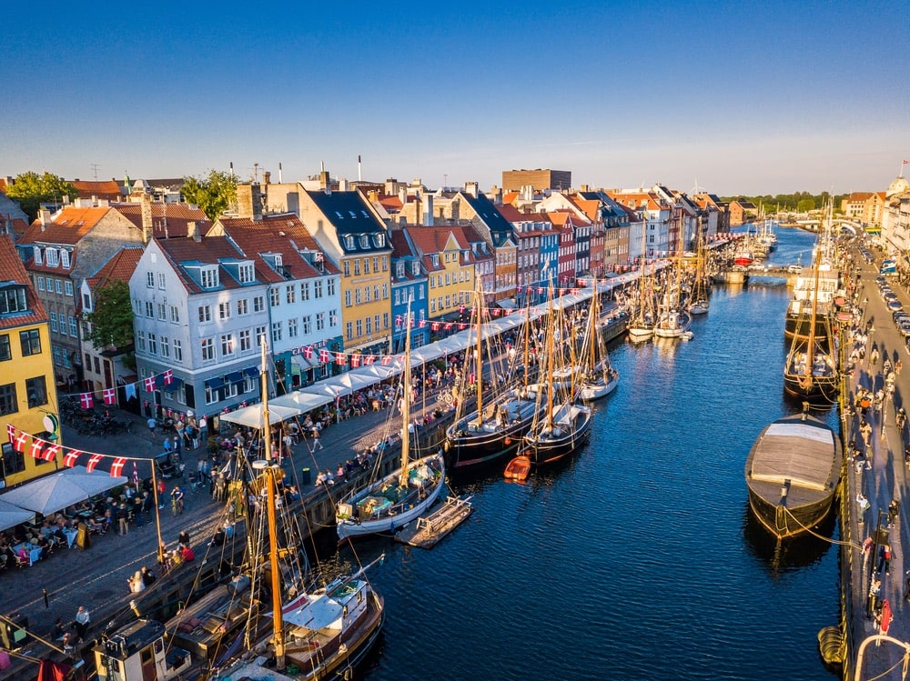Beautiful historical city center. Nyhavn New Harbour canal and entertainment district in Copenhagen, Denmark. The canal harbors many historical wooden ships. Aerial view from the top.